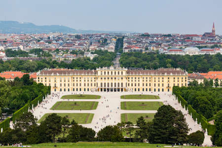 View to Schoenbrunn Palace park in Vienna, Austria with tourists in the foreground.