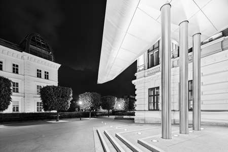Entrance of the Albertina building with its modern roof at night in Austria in black and white