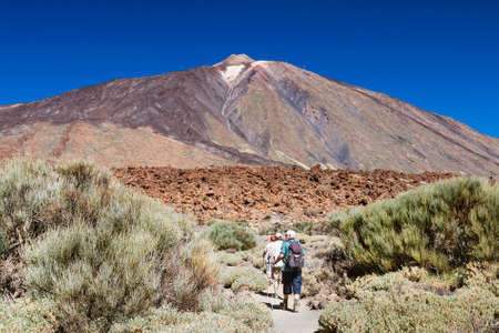 TENERIFE - OCTOBER 10: Tourists walking towards the Pico del Teide through bushes in Tenerife, Spain, with deep blue sky on October 10, 2014 Editorial