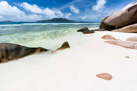 Anse Grosse Roche in La Digue, Seychelles with clear water and granite rocks Stock Photo