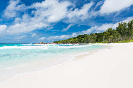 Pristine white beach in La Digue, Seychelles with palm trees and emerald water Stock Photo