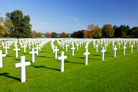 White crosses at the American military cemetery Henri-Chapelle near Aubel in Belgium with blue sky.