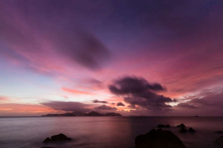 Colorful sunset long exposure with view to Praslin from La Digue, Seychelles with granite rocks in the foreground