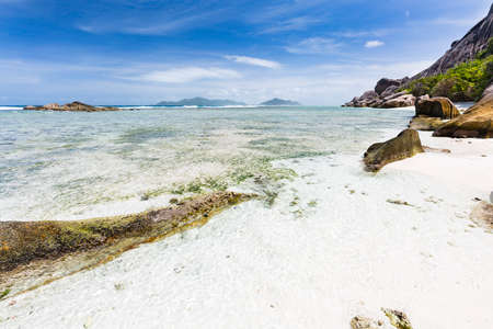 Tropical white beach Anse Pierrot in La Digue, Seychelles with Praslin in the background Stock Photo
