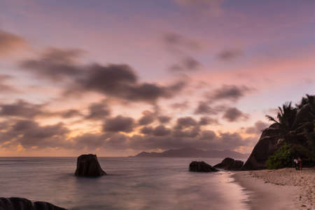 Colorful sunset long exposure at Anse Source D'Argent in La Digue, Seychelles with granite rocks in the foreground