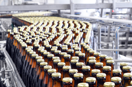 beer filling in a brewery - conveyor belt with glass bottles