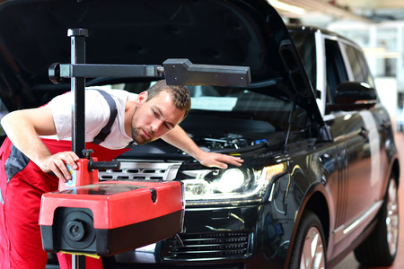 car repair shop - worker checks and adjusts the headlights of a car's lighting system 스톡 콘텐츠