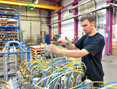 Operator repairs a machine in an industrial plant with tools - pneumatic and hydraulics