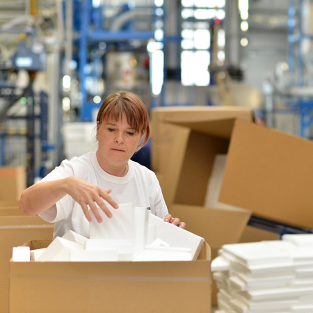 A woman put styrofoam components into packages for the customer. Stock Photo