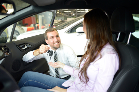car salesman hands over the car key in the car dealership to customers 스톡 콘텐츠