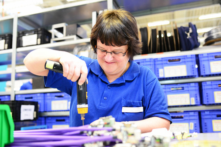 older woman assembles electronic components in a hi tech factory Zdjęcie Seryjne