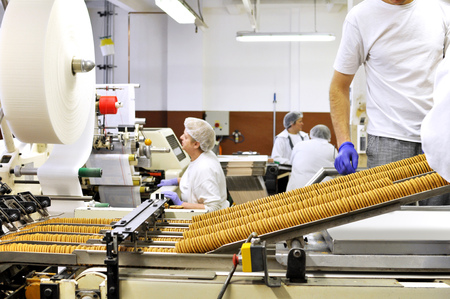 workers sort biscuits on a conveyor belt in a factory - production in the food industry Stock Photo