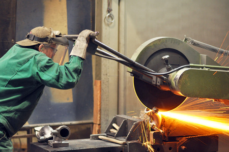 Workers in a foundry grind castings with a grinding machine - Heavy industry workplace