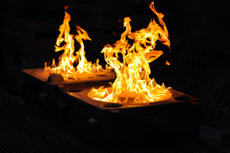 Flames after casting a workpiece in a foundry - production of steel castings at an industrial company