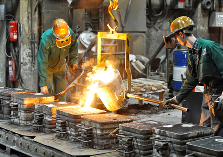 Group of workers in a foundry at the melting furnace - production of steel casting in an industrial company Stockfoto