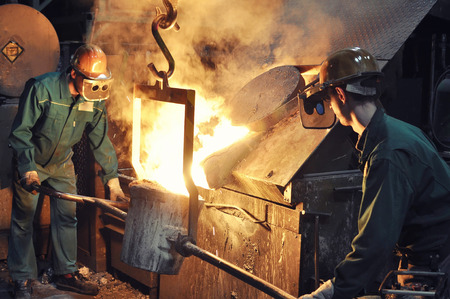 Group of workers in a foundry at the melting furnace - production of steel casting in an industrial company Imagens