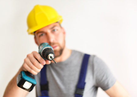 freestanding craftsman construction worker assembler with drilling machine - friendly worker in clothes on white background