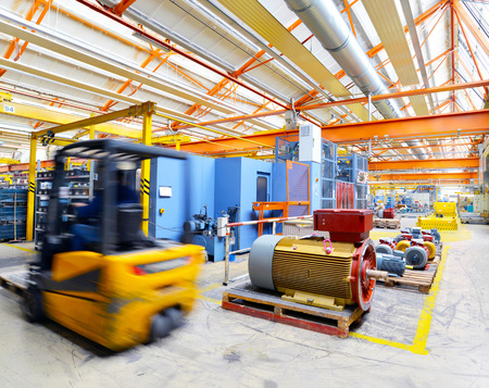 forklift truck drives in an industrial hall - interior in mechanical engineering