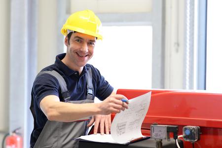 fabrieksarbeiders inspecteren de technologie van een fabriek op functie - assembler in werkkleding Stockfoto