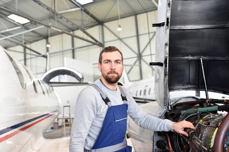 Portrait of an aircraft mechanic in a hangar with jets at the airport - Checking the aircraft for safety and technical function Stock Photo