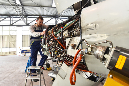 Aircraft mechanic repairs an aircraft engine at an airport hangar