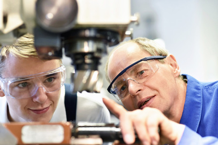 closeup picture: trainer and apprentice in vocational training on a machine - explaining details of the machine Stock Photo