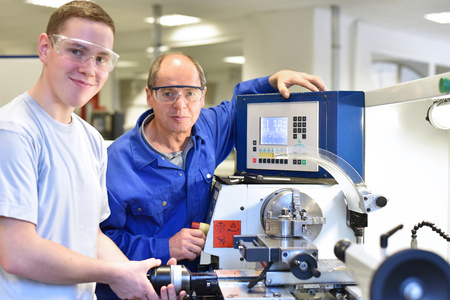 portrait apprentice and teacher in vocational training at a cnc lathe