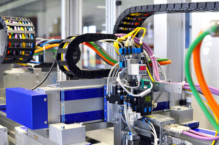 details of a machine with pneumatic lines in industrial production for electronic components