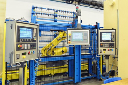 industrial robot with control unit in a factory for mechanical engineering