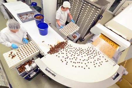 Herstellung von Pralinen in einer Fabrik für die Lebensmittelindustrie - Förderbandarbeiter mit Schokolade Standard-Bild