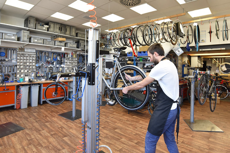 friendly and competent bicycle mechanic in a workshop repairs a bike Stock Photo