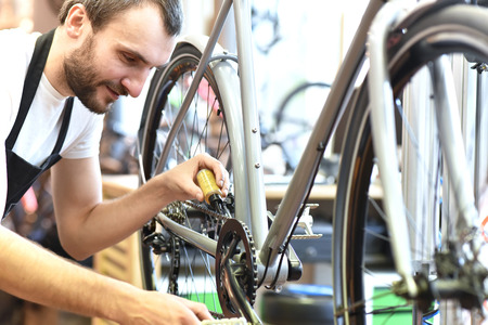 mechanic in a bicycle repair shop oiling the chain of a bike