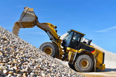 heavy construction machine in open-cast mining - wheel loader transportation gravel in a gravel plant