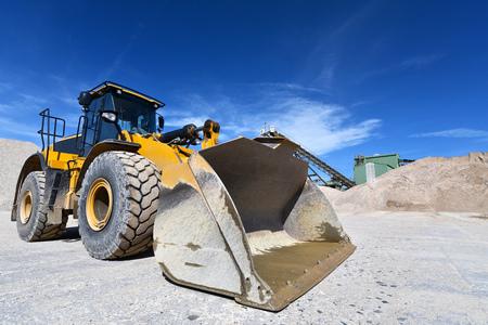 heavy construction machine in open-cast mining - wheel loader transportation gravel in a gravel plant