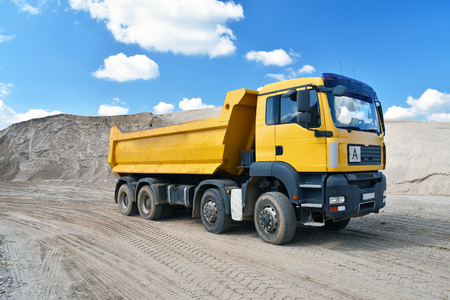 Truck transports sand in a gravel pit - gravel mining at an open pit mine
