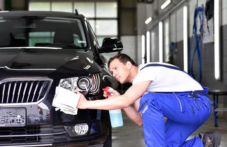 lavado profesional de automóviles: el trabajador de un concesionario de automóviles pule la pintura del automóvil