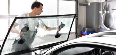 Mechanic in a garage replaces defective windshield of a car Archivio Fotografico - 97709068