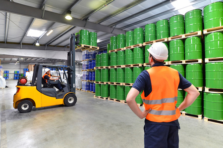 group of workers in the logistics industry work in a warehouse with chemicals Stock Photo