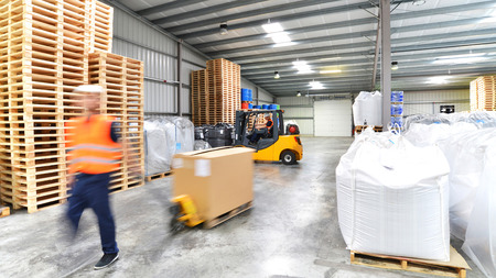 transport and logistics in a warehouse of a forwarding agent - worker with a lift truck 免版税图像