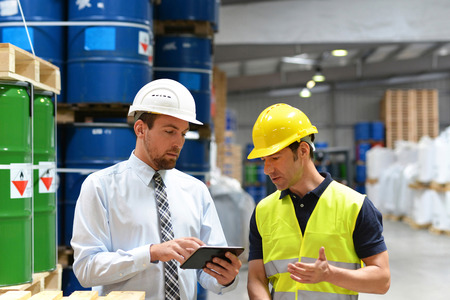 managers and workers in the logistics industry talk about working with chemicals in the warehouse Stock Photo