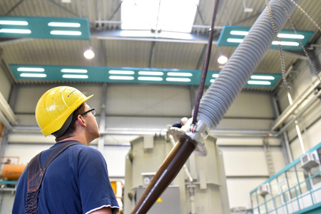 Operator installs a transformer in an industrial plant in mechanical engineering