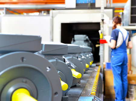 manufacture of modern electric motors in an industrial company - construction and assembly workers Reklamní fotografie - 105744904