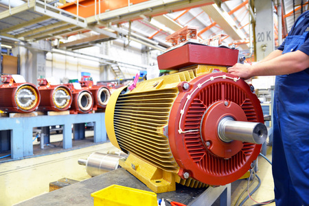 manufacture of modern electric motors in an industrial company - construction and assembly workers Reklamní fotografie - 105744984