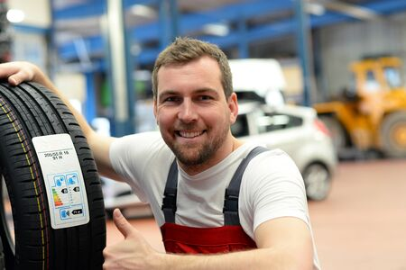 Economy sticker with consumption values on a new car tire - changing tires in the workshop by mechanical means