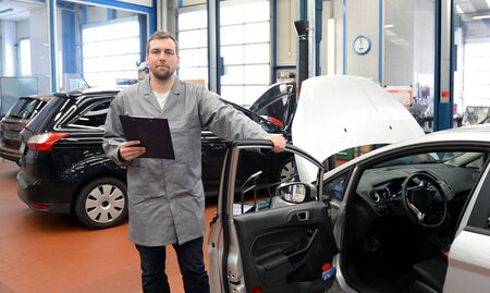 car mechanic in a workshop with checklist - engine repair and diagnosis on a vehicle Reklamní fotografie