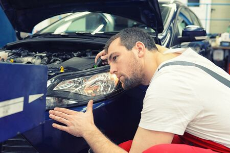 adjusting the headlights on the car by mechanics in a garage