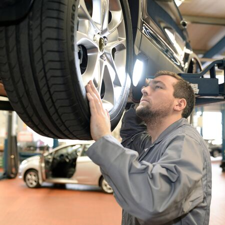Mechanic in a workshop checks and inspects a vehicle for defects Reklamní fotografie