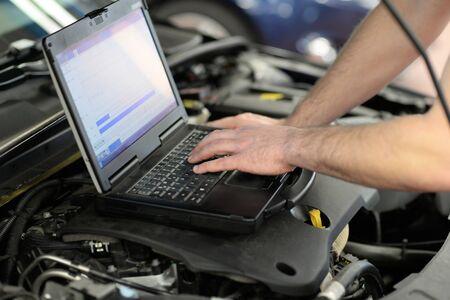 Diagnóstico de vehículos modernos con computadora en un garaje: el mecánico inspecciona y actualiza el software. Foto de archivo