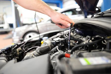 car mechanic in a workshop repairing a vehicle
