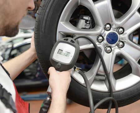 auto mechanic checks the air pressure of a tire in the garage